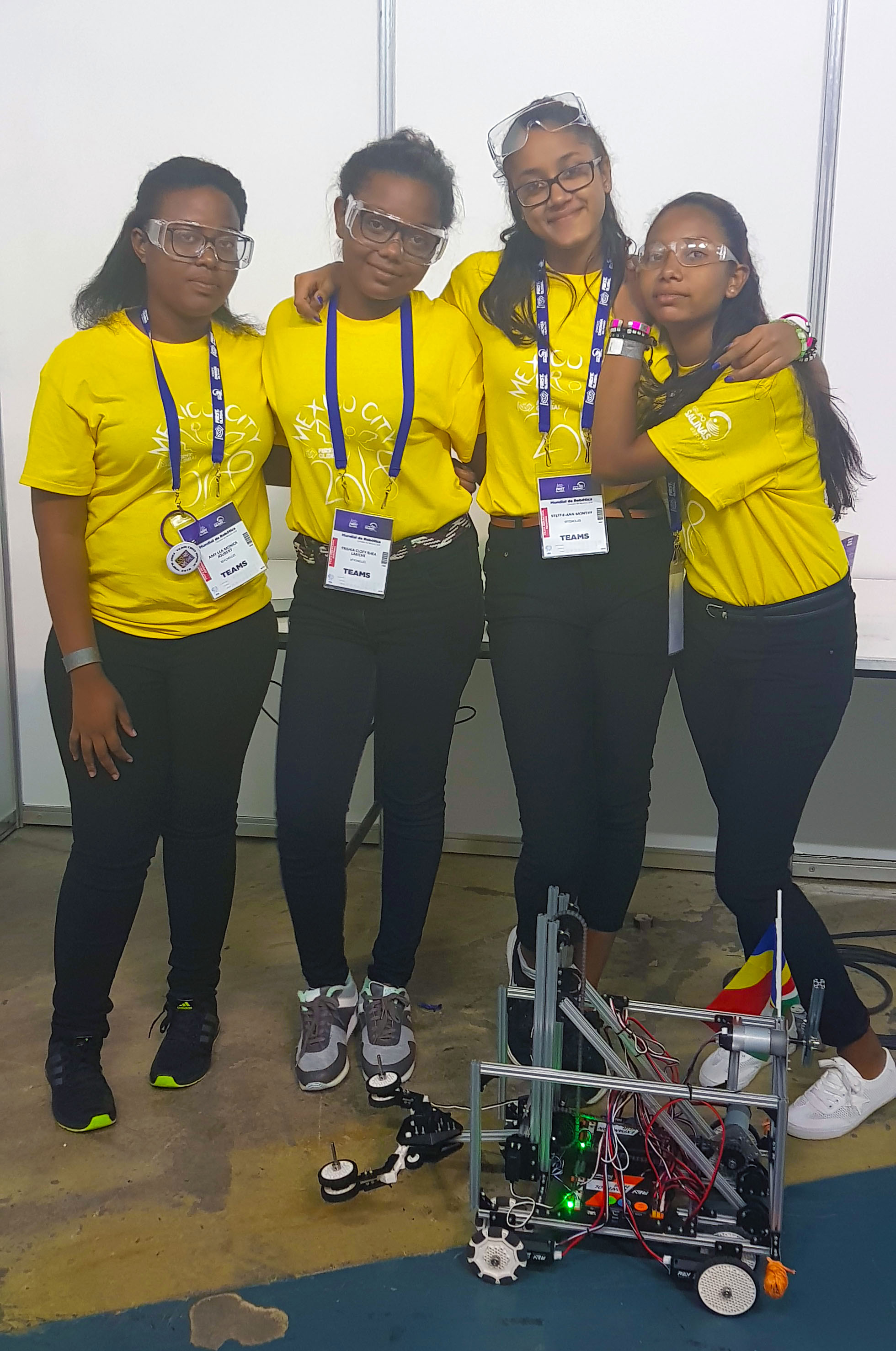 four girls in yellow shirts standing with a robot