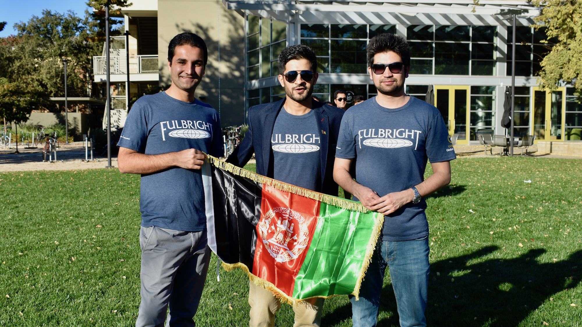Students pose outside the UC Davis International Center with the flag of Afghanistan.