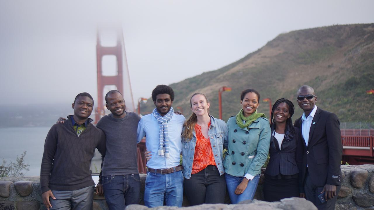 group of young people standing in front of the golden gate bridge