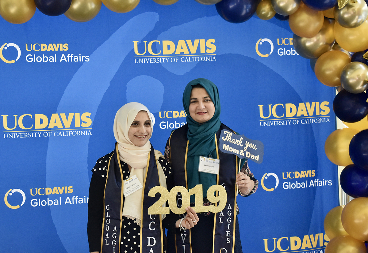 two women in hijab standing in front of a blue background with balloons holding a sign that says 2019
