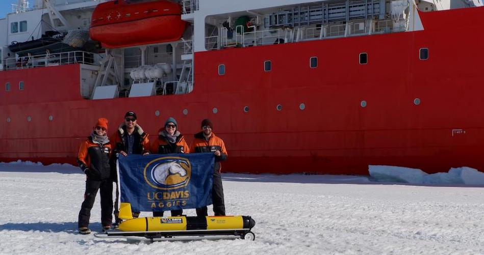 UC Davis doctoral students Cordielyn Goodrich, Andrew Friedrichs and Jasmin McInerney with EPFL's Sebastian Lavanchy and the glider Storm Petrel on the ice beside icebreaker R/V Araon at Jang Bogo Station in Antarctica, January 2019. (Joe Haxel, OSU/NOAA)