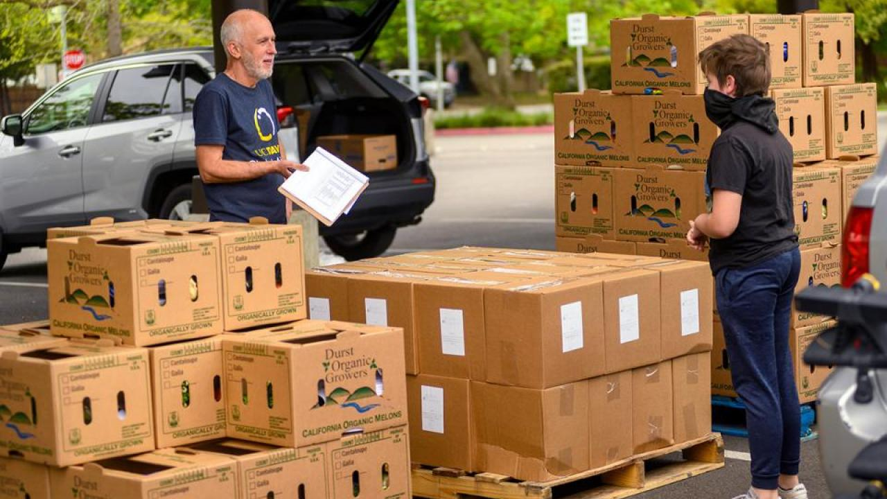 Robb Davis, left, has taken a leave of absence from Global Affairs to oversee the Yolo Food Bank's coronavirus response. He's coordinating food delivery, like this distribution at Davis High School.