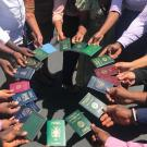 Mandela Fellows holding passports in a circle