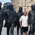The 5th Beatle: Gonzales stands among four statues commemorating the members of The Beatles on a London street. (Courtesy Adrian Gonzales)